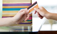 a shopper hands over a credit card