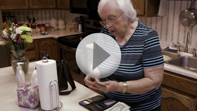 Older woman in her kitchen looking through wallet contents