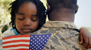 A U.S. veteran hugging his daughter while she holds a mini United States flag