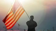 Military person waving an American flag